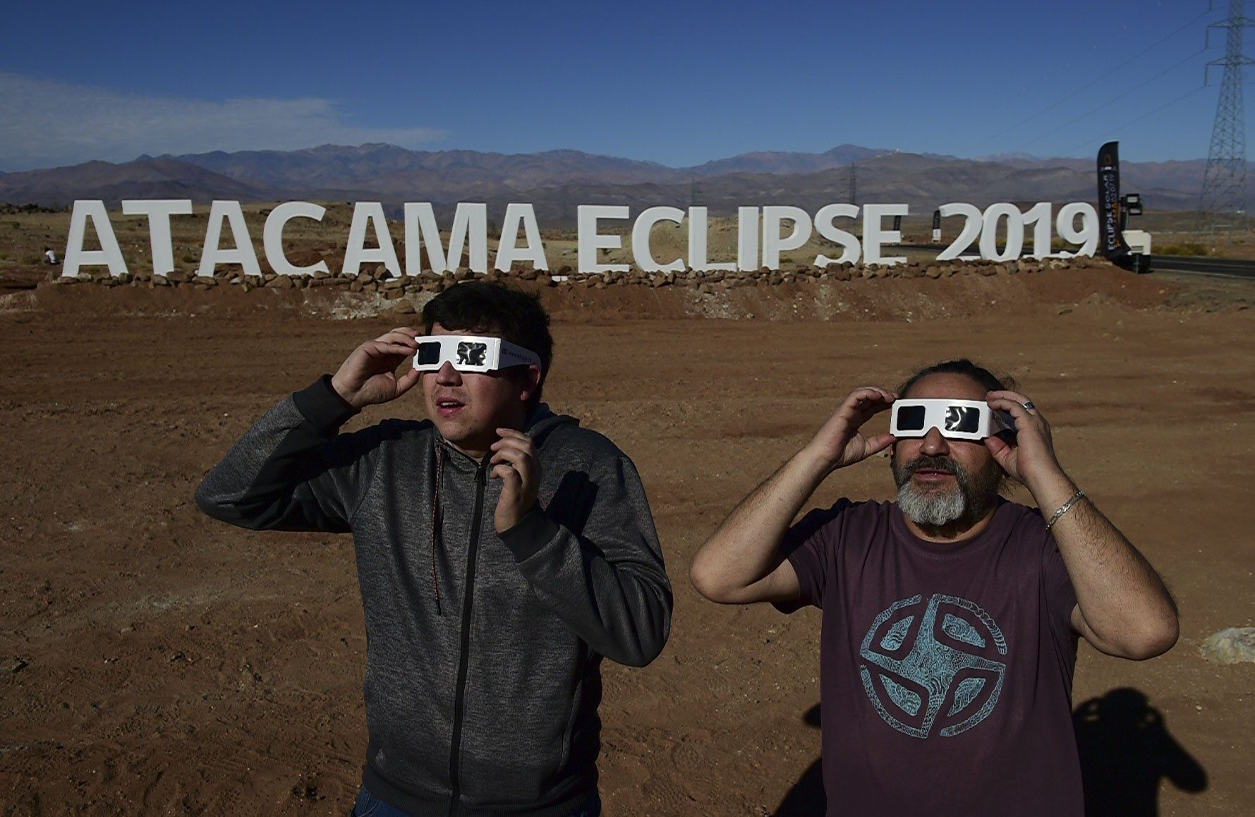 Turistas prueban gafas especiales para ver un eclipse en la entrada de un campamento astronómico en la comuna de Vallenar en el desierto de Atacama. (Foto: AFP)