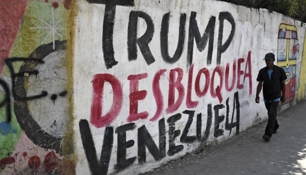 """Nicolás Maduro suspendió el diálogo por el bloqueo de Estados Unidos y el apoyo de Juan Guaidó a estas. En la foto, un muro con la pinta """"Trump desbloquea a Venezuela"""" en Caracas. (Foto: AFP)"""