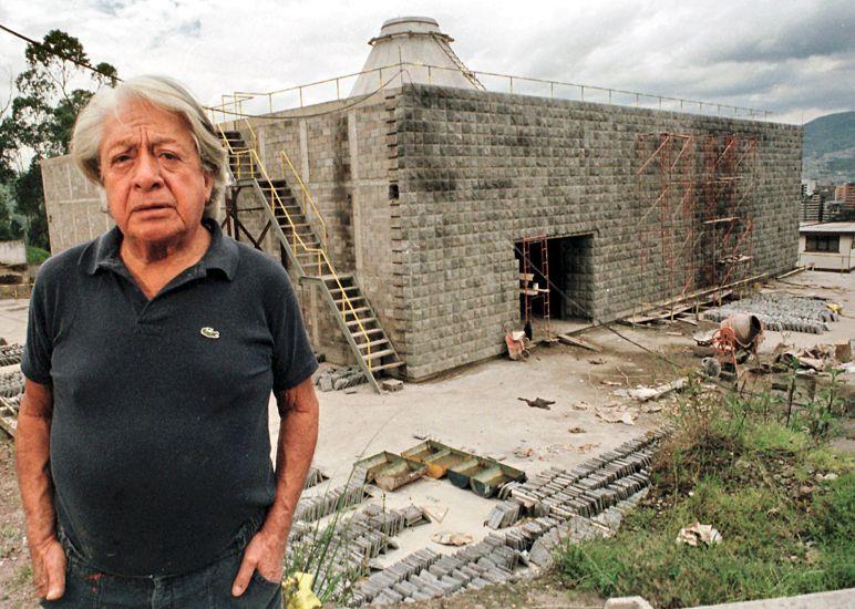 """El pintor ecuatoriano Oswaldo Guayasamin posa con el fondo de la """"Capilla del Hombre"""" un museo diseñado por él, en Quito, en noviembre de 1998. [Foto: AFP]"""
