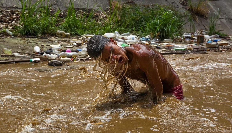 Desesperados por la crisis, jóvenes se buscan la vida entre las aguas fecales de Caracas | FOTOS