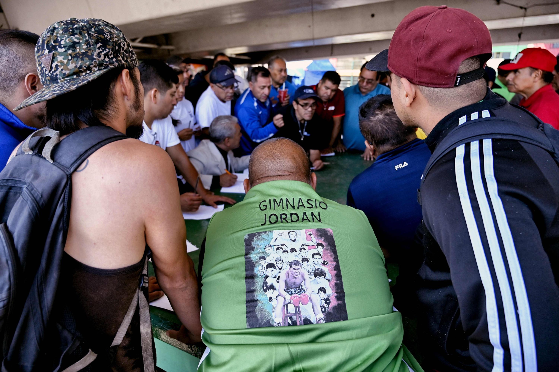 Los entrenadores de diferentes gimnasios revisan las listas para colocar a sus boxeadores en las peleas en el Gimnasio Ramírez en Ecatepec. (Foto: AFP)
