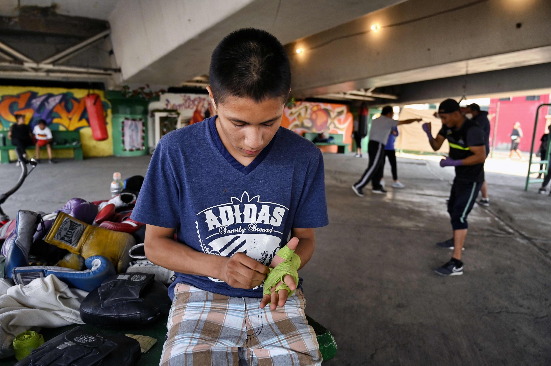 Un niño se pone vendas en la mano antes de una sesión de entrenamiento en el Gimnasio Ramírez. (Foto: AFP)