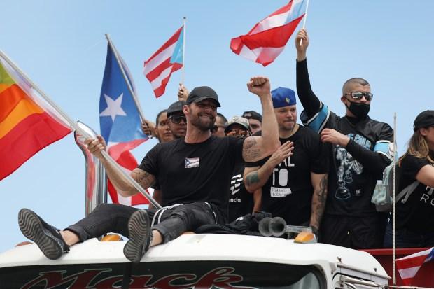 Ricky Martin, junto al rapero René Pérez, también conocido como Residente, marchan a lo largo de la carretera Las Américas en una huelga nacional que exige la renuncia de Ricardo Rosselló. (Foto: AFP)