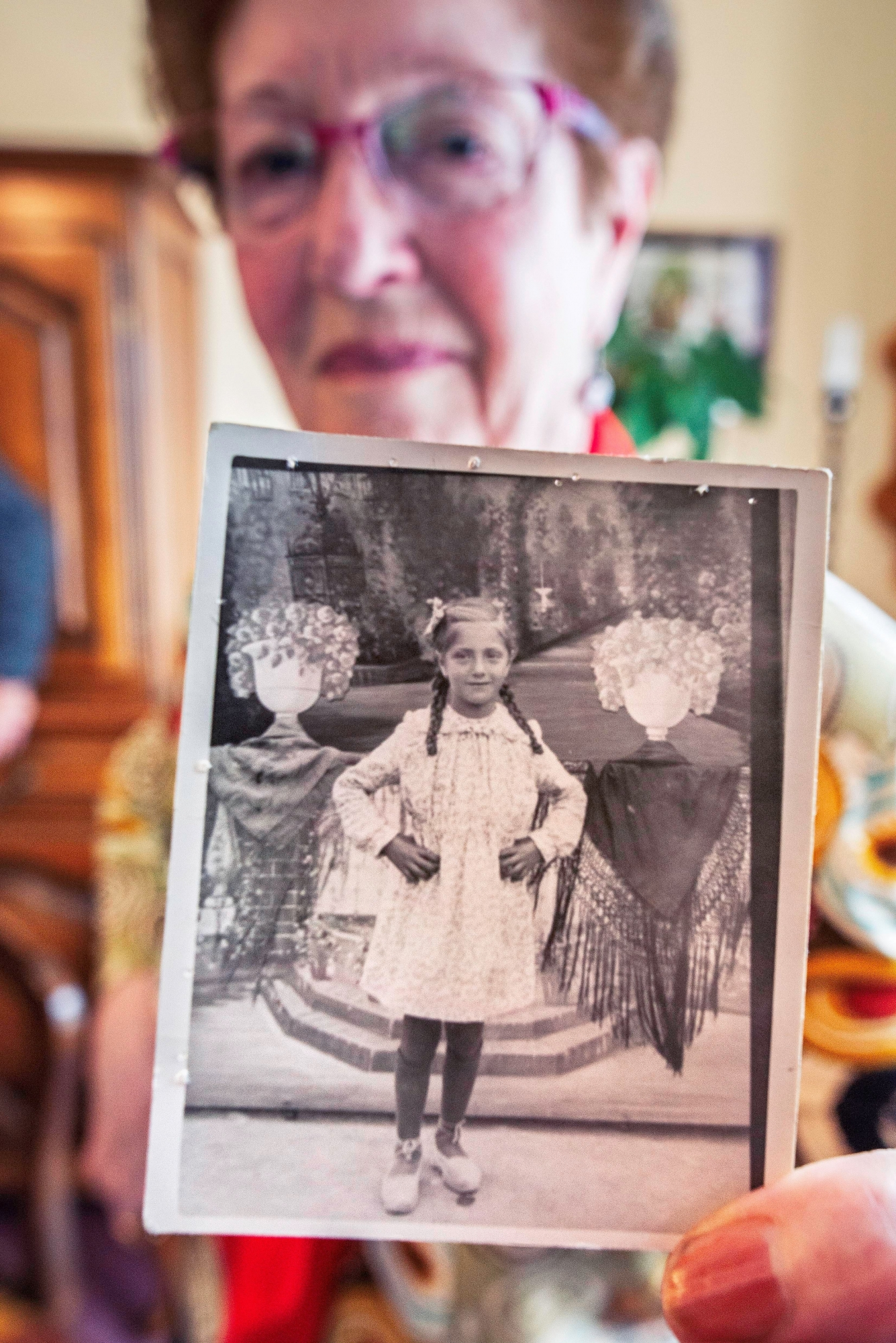 Paquita González muestra la foto que la hicieron de niña, una de las escasas posesiones que le confiscaron a su padre, Francisco, cuando ingresó en un campo de concentración nazi. (EFE)<br>