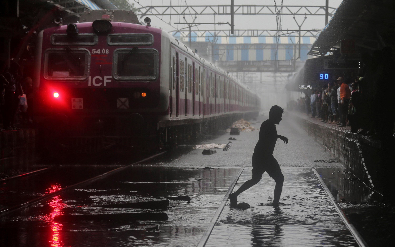 Un viajero cruza las vías del tren afectadas por las lluvias. (Foto: Reuters)