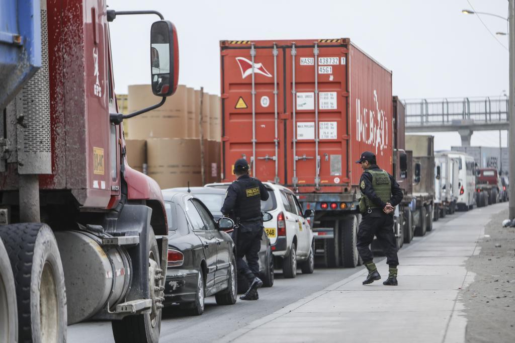 Camiones en la avenida Nestor Gambeta. Motociclista. Congestion vehicular. Policias cruzando pista. CALLAO. CONGESTION VEHICULAR.