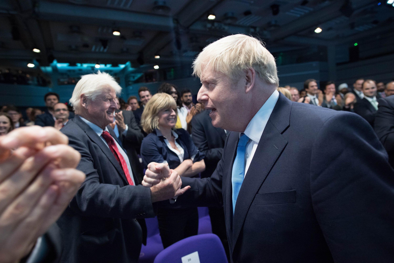 Boris Johnson le da la mano a su padre Stanley Johnson tras el anuncio oficial. (Foto: AFP)